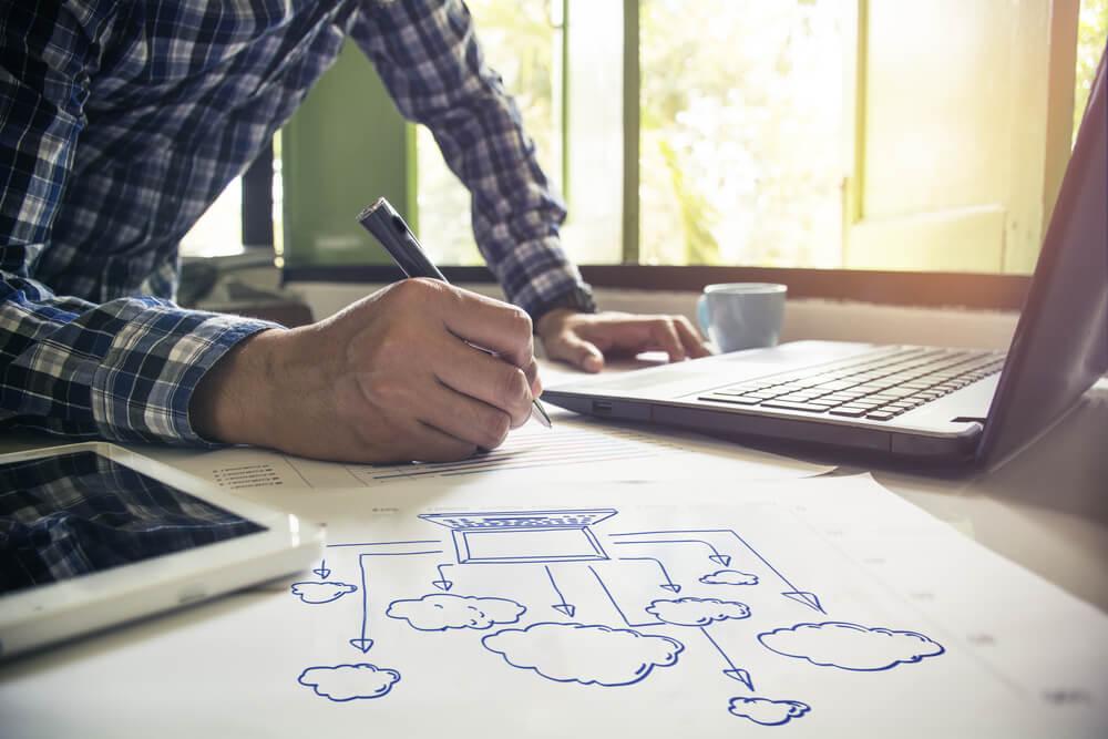 mão masculia fazendo anotações sobre desenho de cloud computing