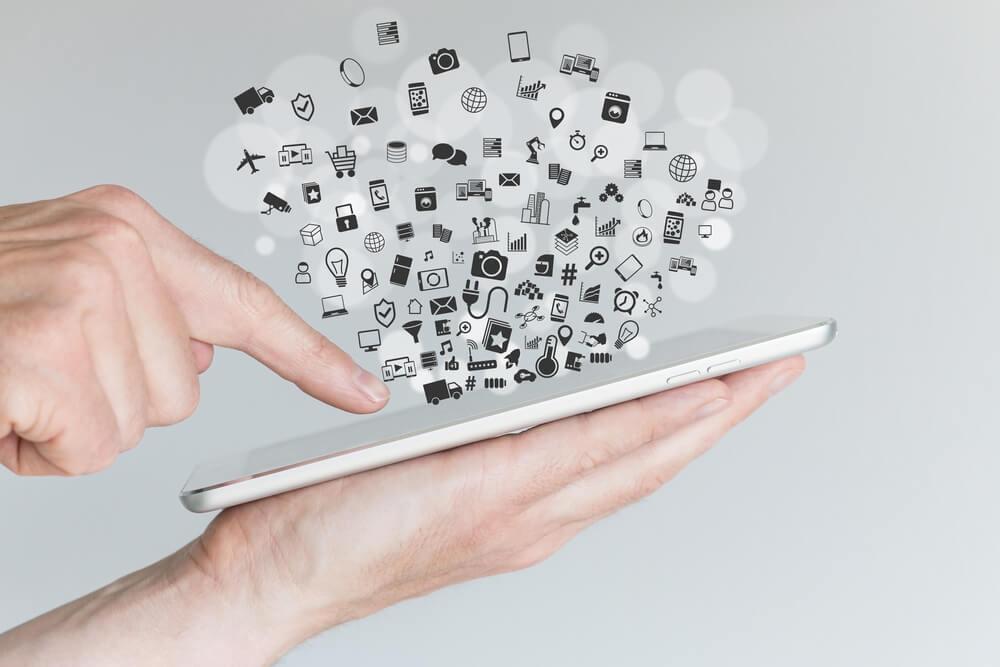 mão masculina segurando tablet cercado de símbolos ligados a criatividade