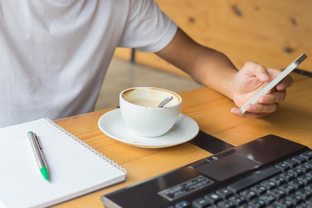 mão masculina segurnaod smartphone próximo de laptop, caderno e xicara de café