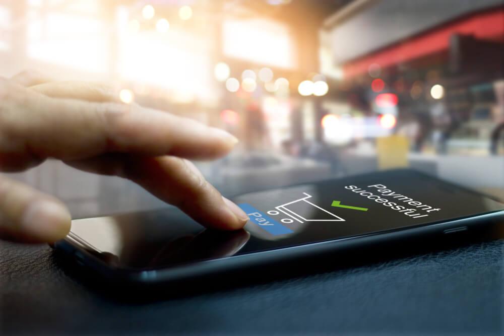 mão masculina tocando smartphone com tela de pagamento com sucesso