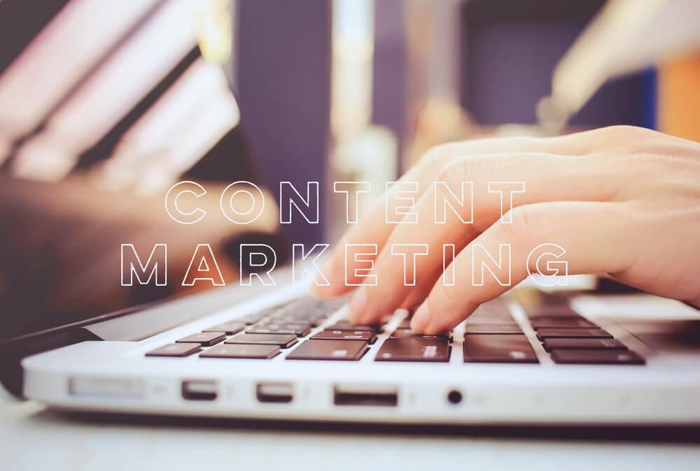mãos acessando laptop com título conteúdo de marketing no inglês