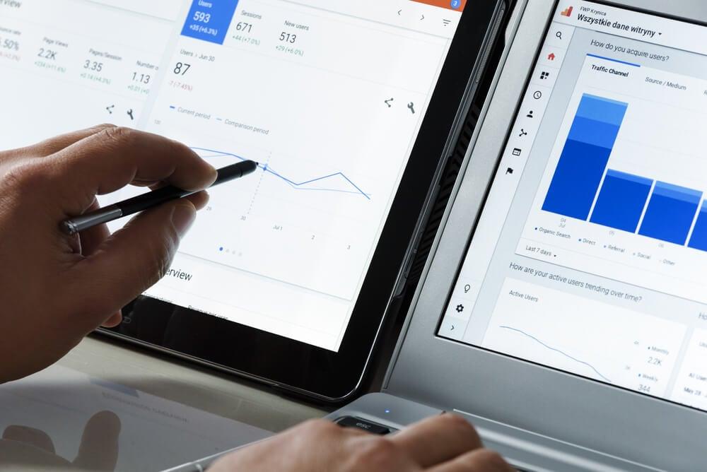 mãos analisando resultados de gráfcos em telas de laptops