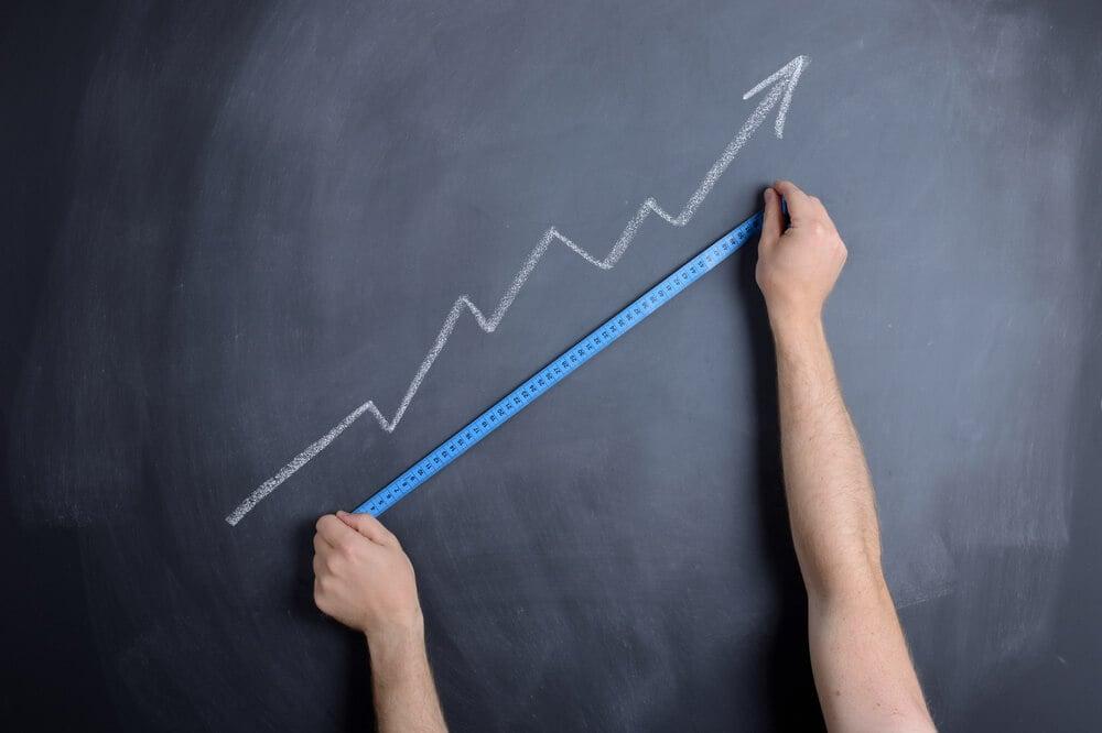 mãos com fita métrica medindo símbolo de crescimento desenhado na parede em giz