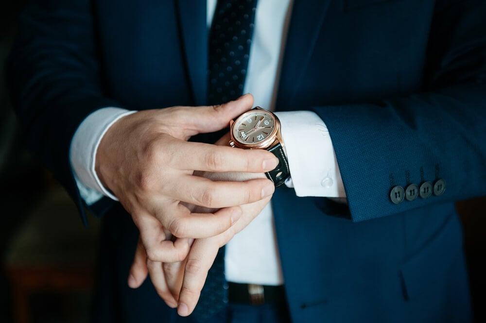 mãos masculinas segurando relógio de puls