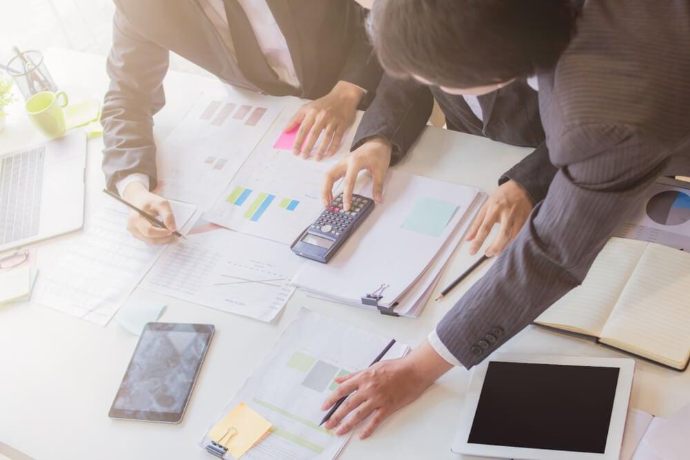 mesa de escritório com papéis com gráficos calculadoras e anotações