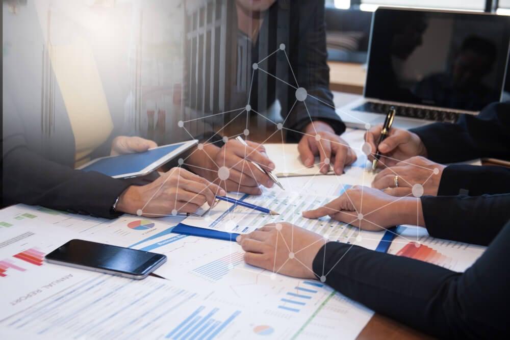 mesa de escritório com vários papéis com gráficos sendo analisados por equipe
