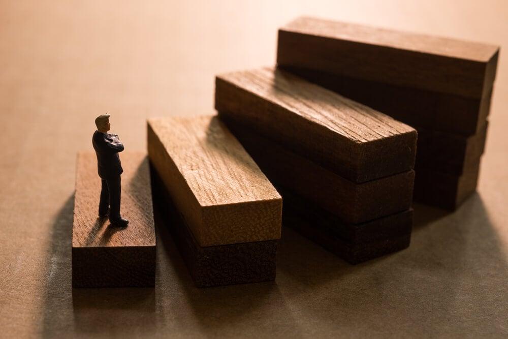 mini boneco embaixo de blocos representando degraus