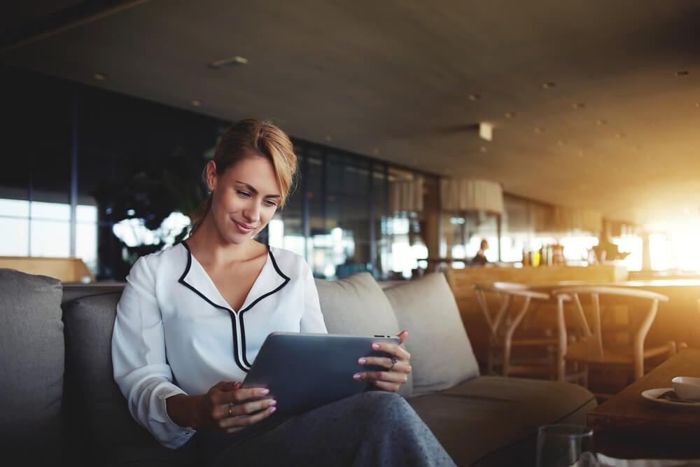 moça acessando tablet em casa ensolarado