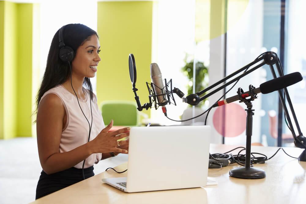 moça em gravação de áudio com fones de ouvido e a frente do laptop