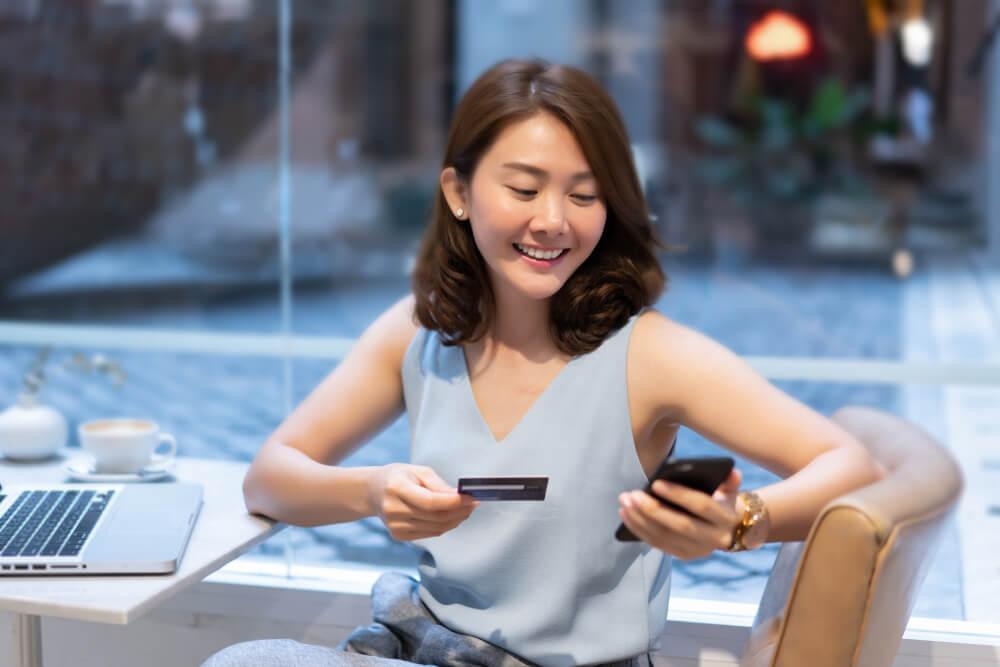 moça sorridente com smartphone e cartão de crédito