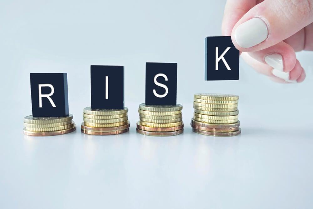 moedas e letras montando a palavra risco em ingles