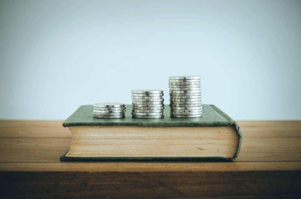 moedas sobre livro e mesa de madeira