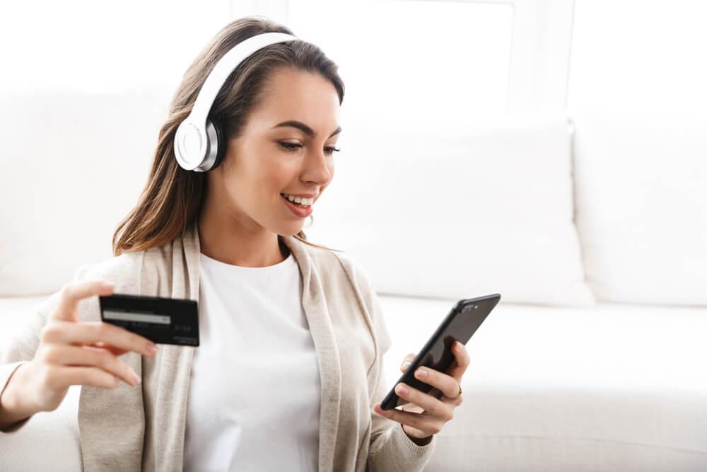 mulher acessando smartphone com fones de ouvido e segurando cartão de crédito