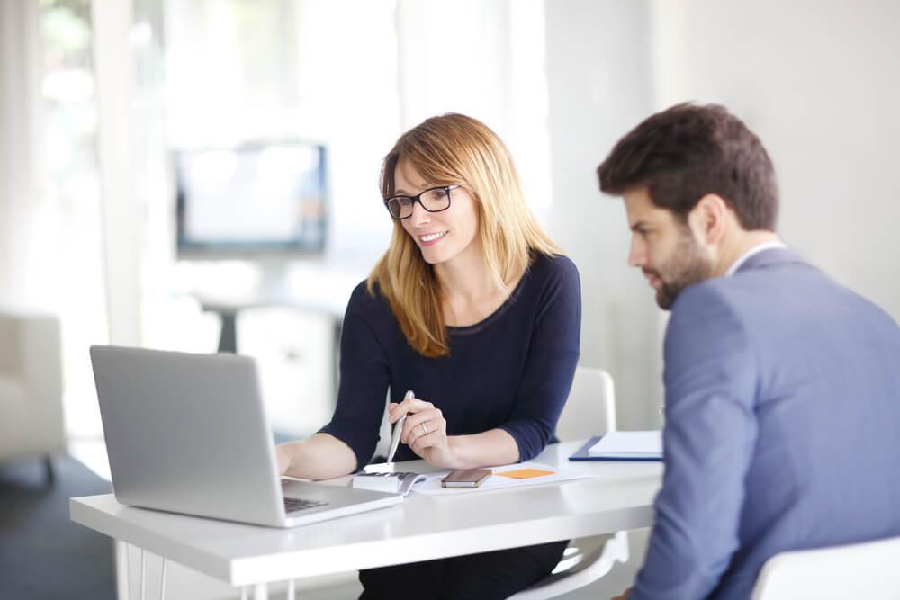 mulher mostrando algo em laptop para homem em ambiente corporativo