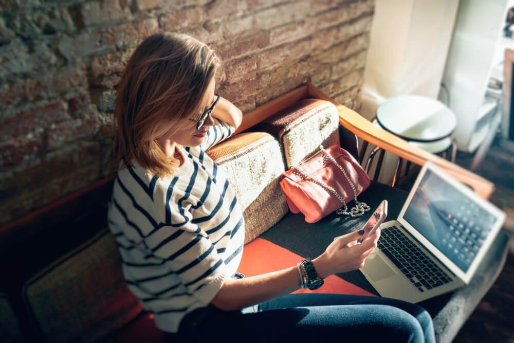 mulher sentada em sofá informal junto do laptop e acessando smartphone