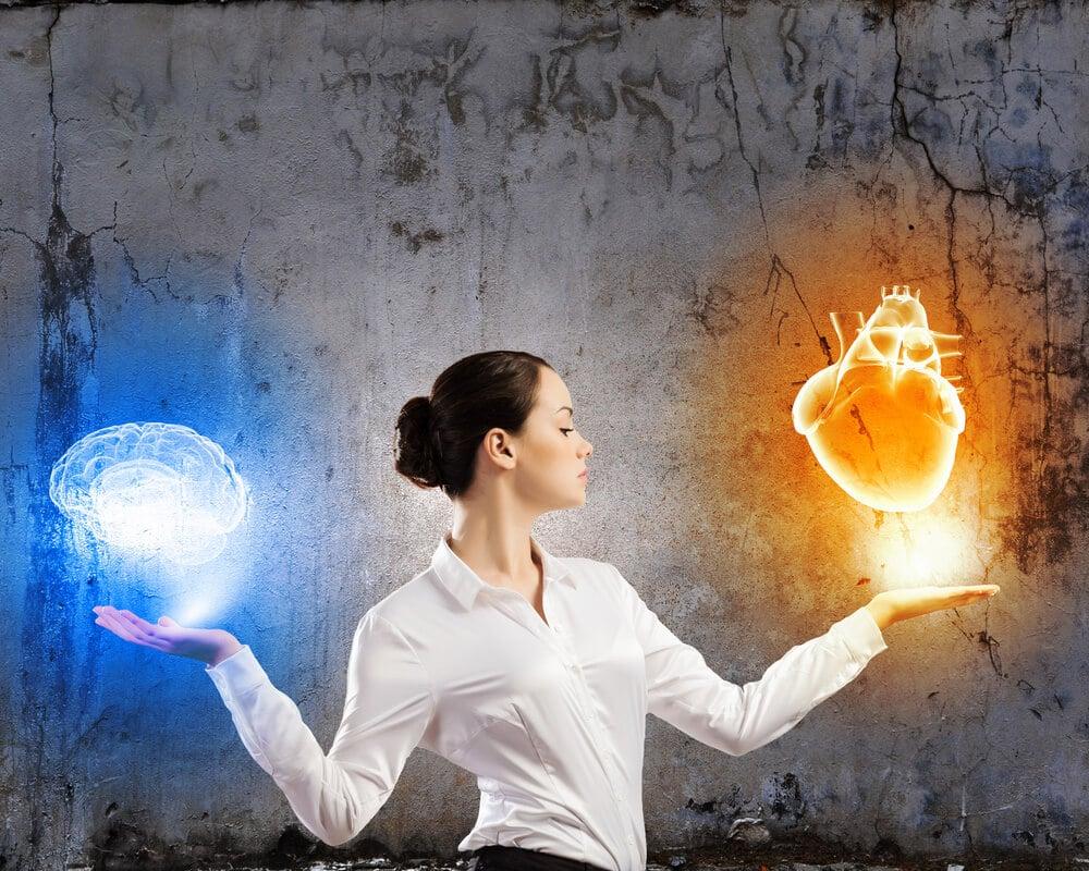 mulher séria segurando símbolos de coração e cérebro representando equilíbrio