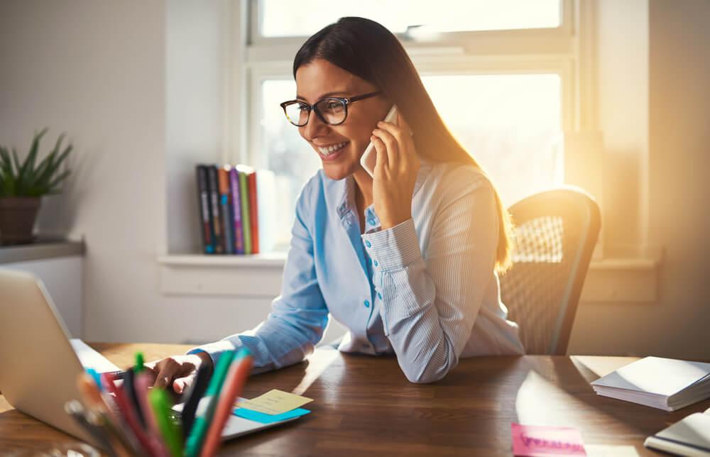 mulher sorridente ao telefone e trabalhando em laptop