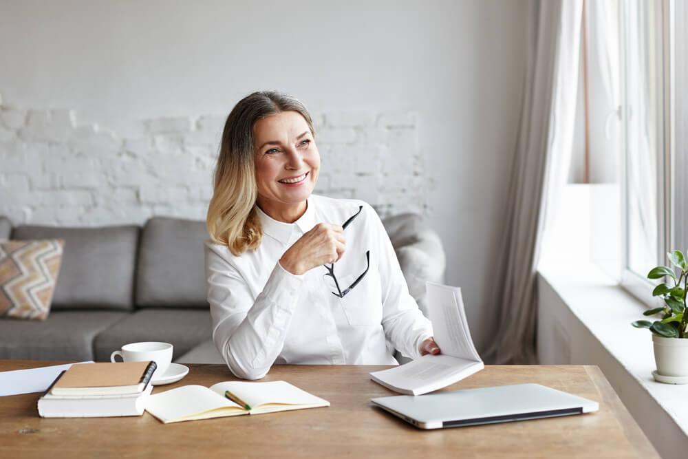 mulher sorridente enquanto trabalha em mesa