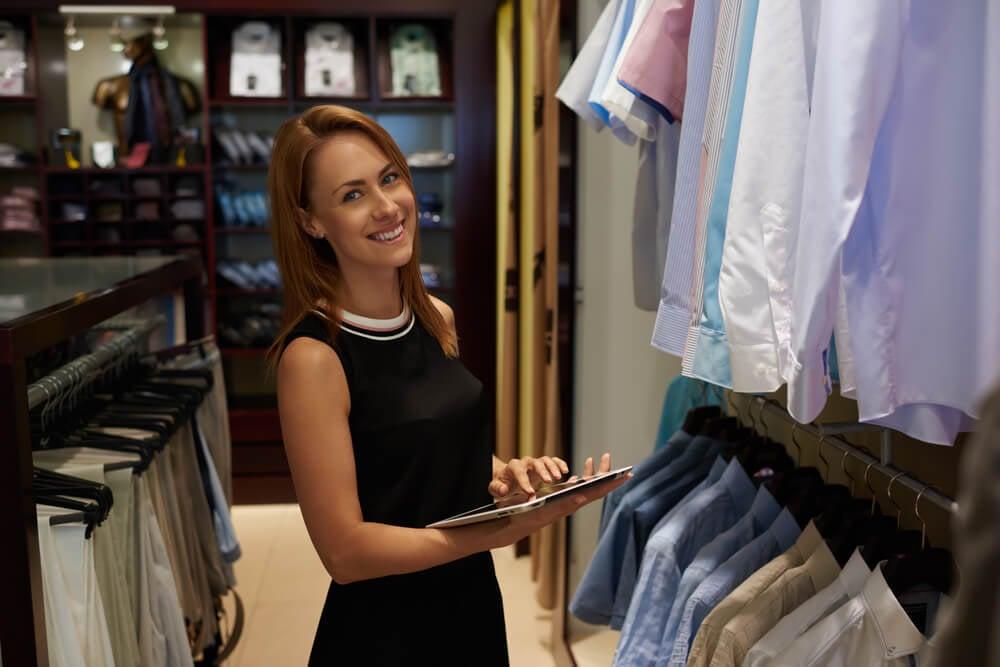 mulher sorridente segurando tablet em loja de camisas