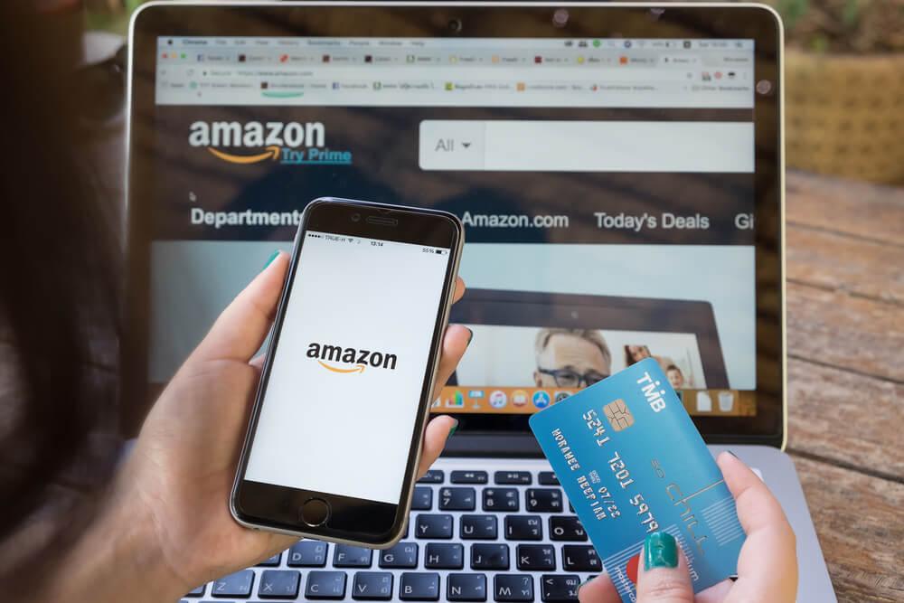 página da WEB e aplicativo mobile da Amazon em notebook, celular e um cartão de crédito