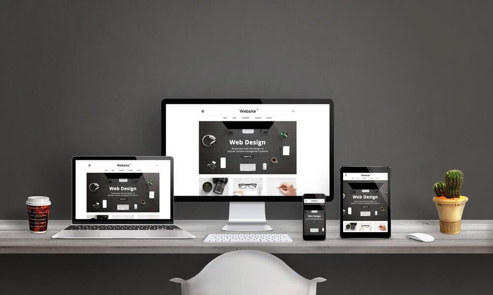 página web em diversos dispositivos em cima de mesa de escritório