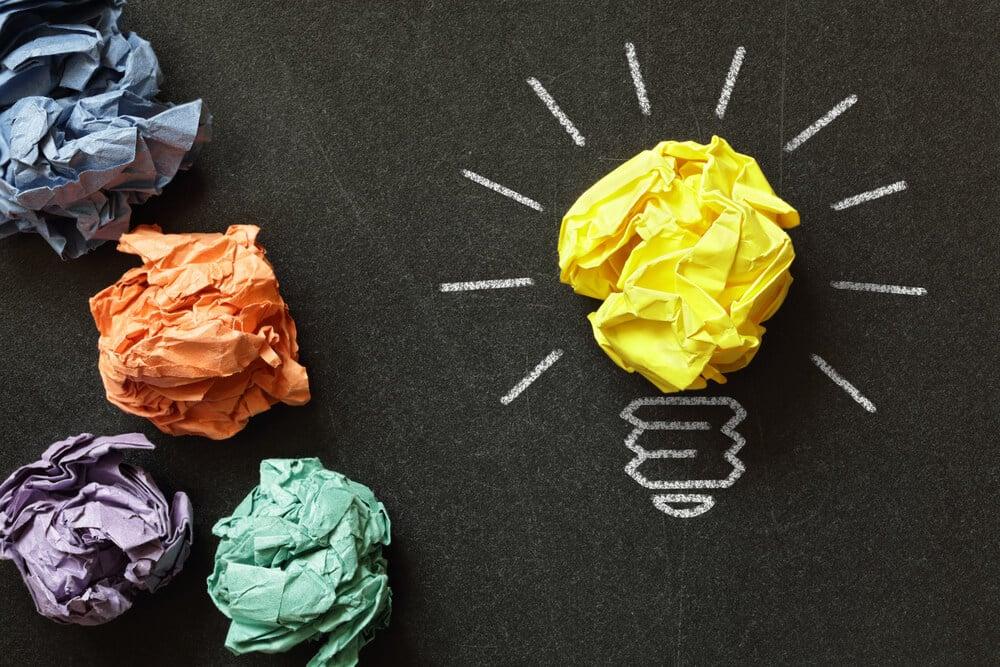 papéis coloridos amassados e um formando uma lâmpada