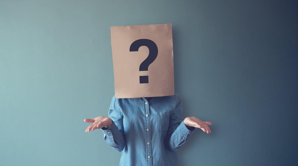 pessoa com dúvida representada pelos sinais com as mãos e saco de papel na cabeça com ponto de interrogação