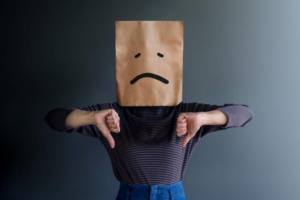 pessoa fazendo sinais negativos e saco de papel na cabeça representando carinha triste