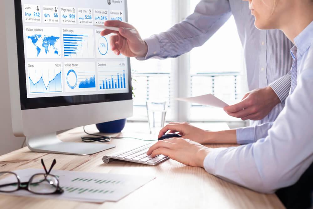 profissionais executivos em análise de gráficos em computador