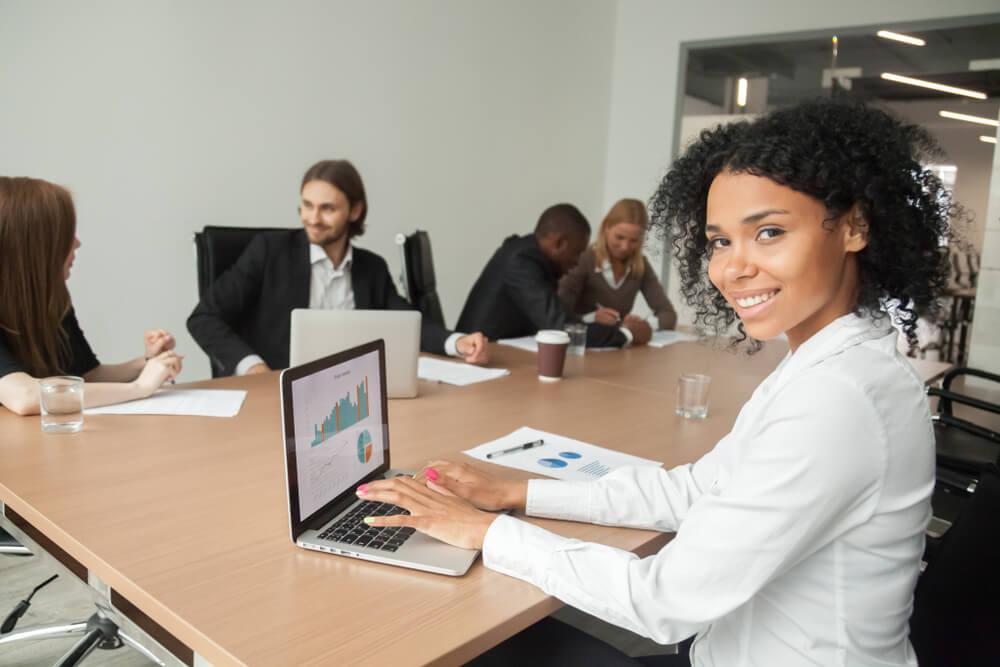 profissional acessando planilhas no laptop em reunião de equipe