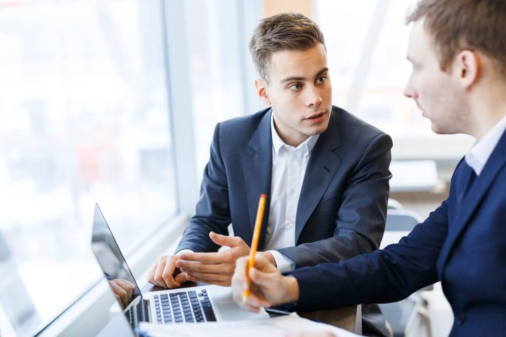 consultor de vendas em conversa com parceiro em frente a laptop