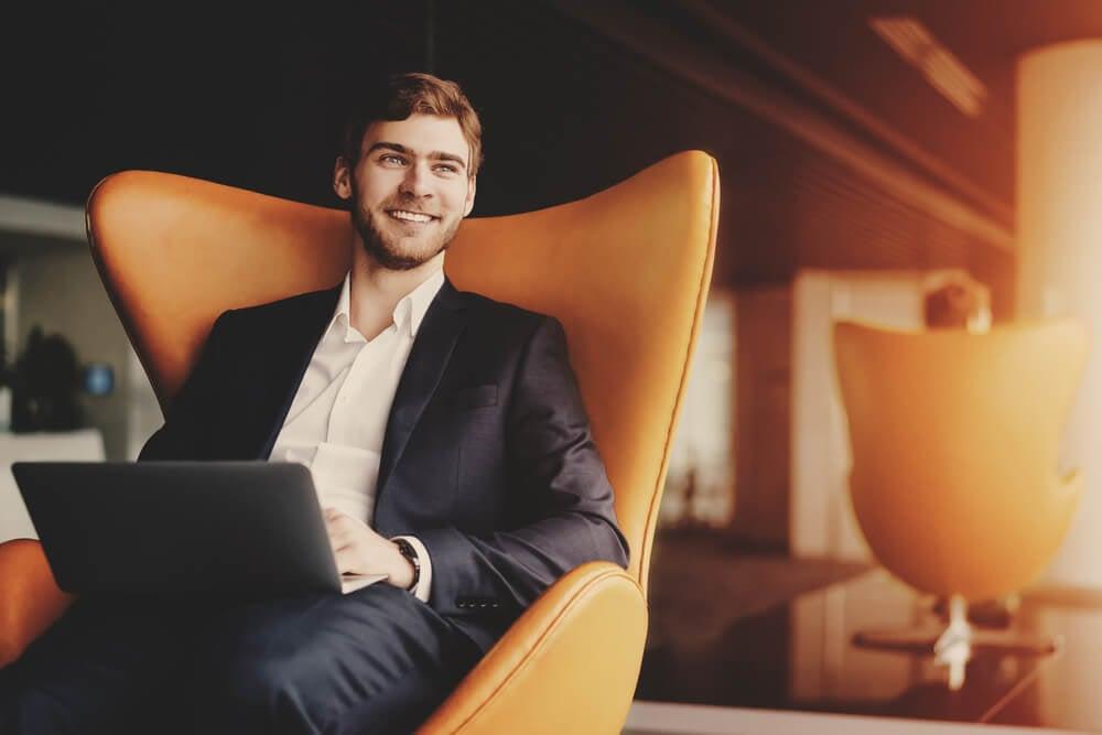 profissional sorridente sentado com laptop no colo