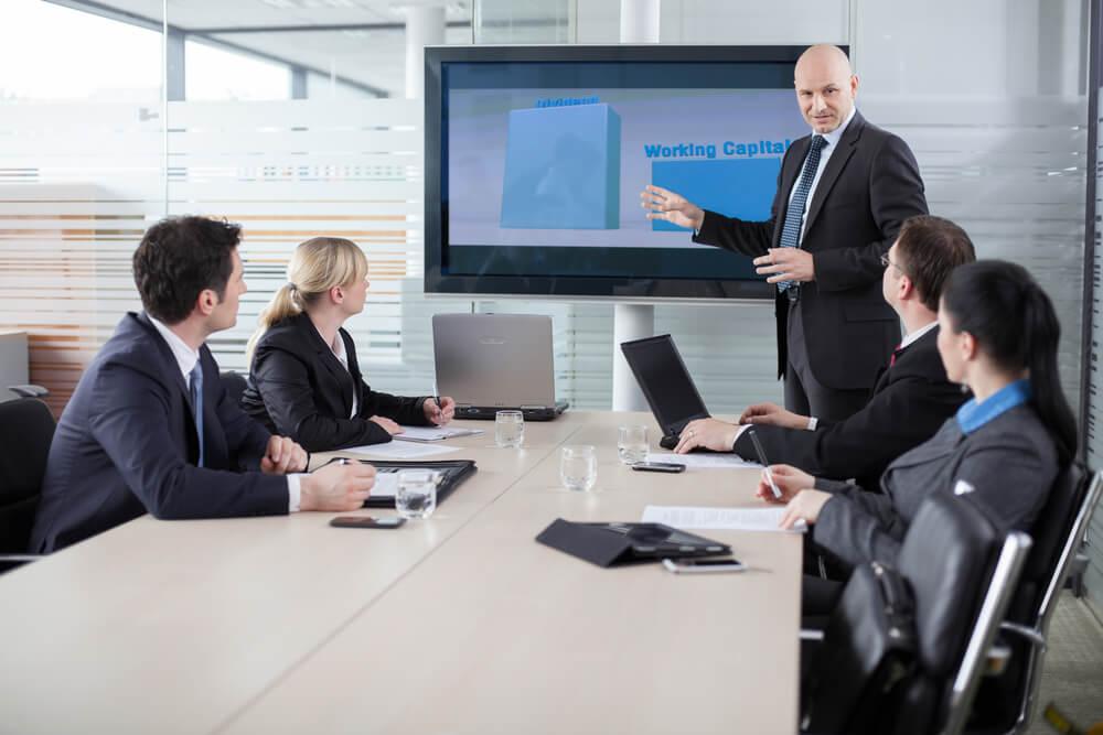 reunião empresarial com homem apresentando gráficos em tv