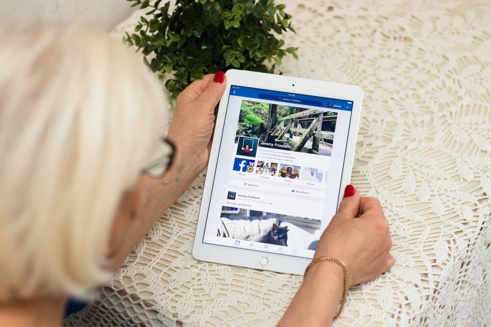 senhora acessando publicações no facebook através do tablet