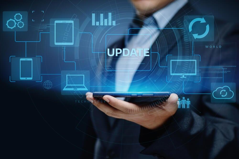 símbolos sobre tecnologia e atualizações acima de tablet segurado por homem de terno