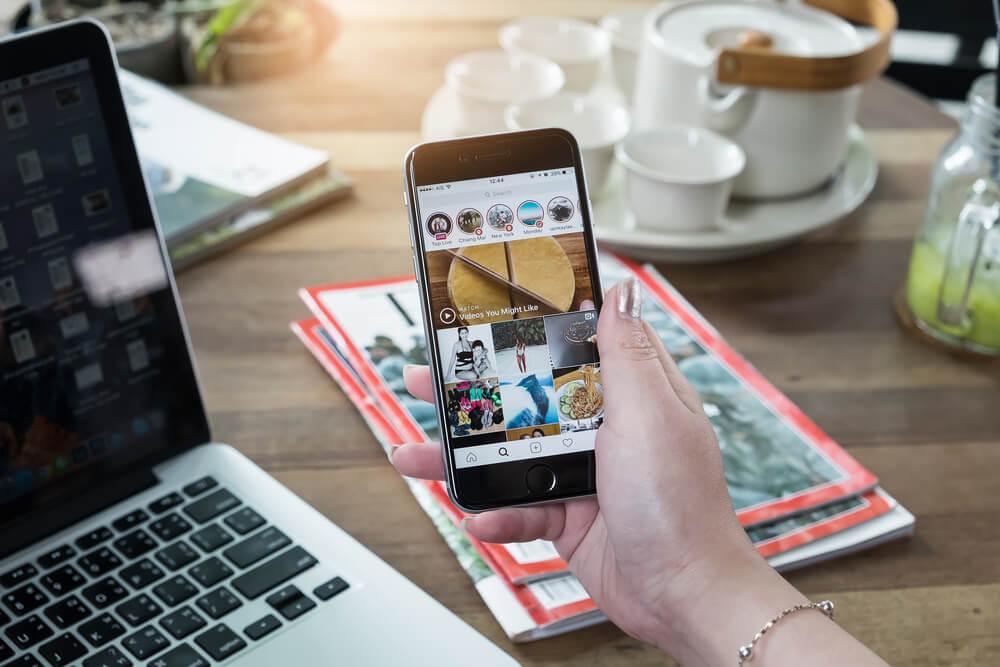 smartphone acessando instagram junto a laptop em mesa de café