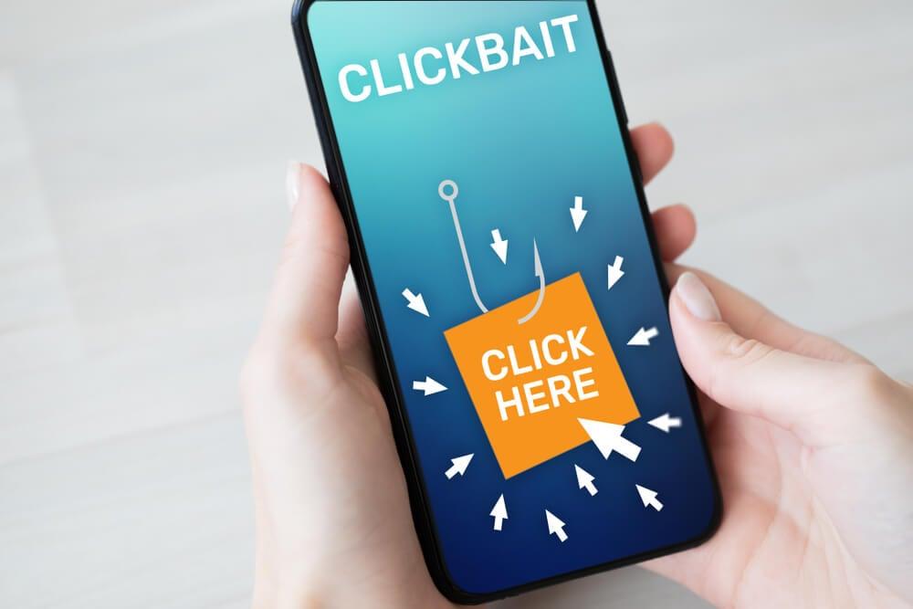 smartphone com imagem clickbait e anúncio clique aqui