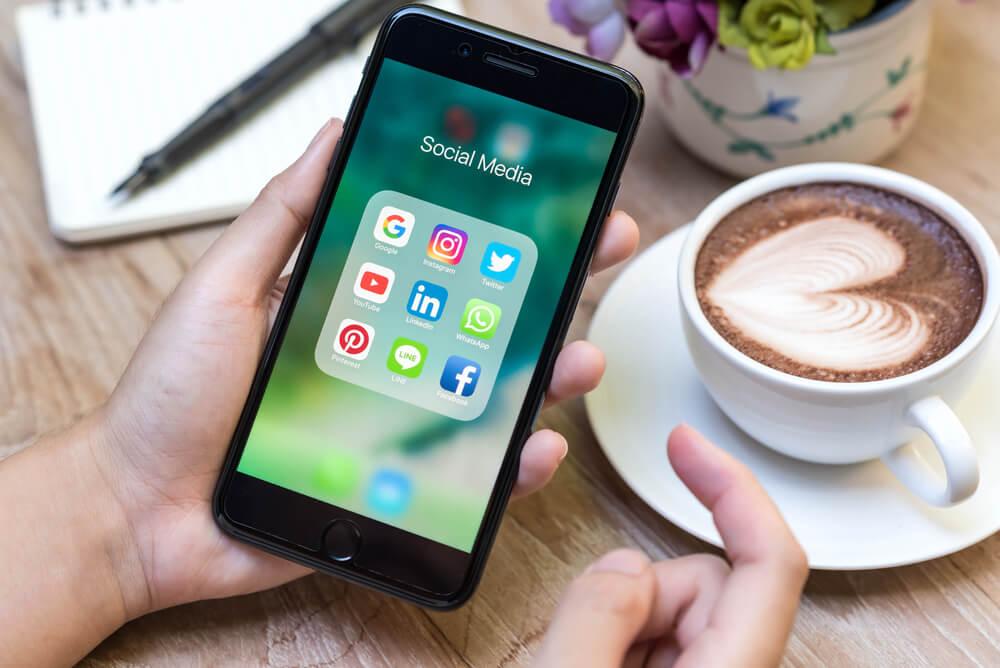 smartphone na tela da pasta de midias sociais em mesa com xícara de café