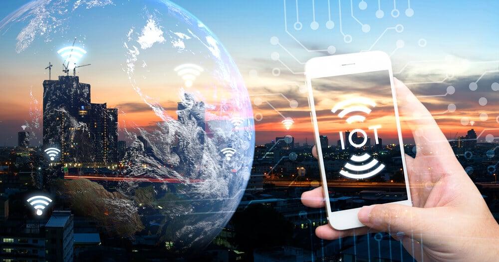 sobreposição de imagem de cidade com planeta terra símbolos de wifi e mão segurando smartphone co sigla de Internet das Coisas em inglês