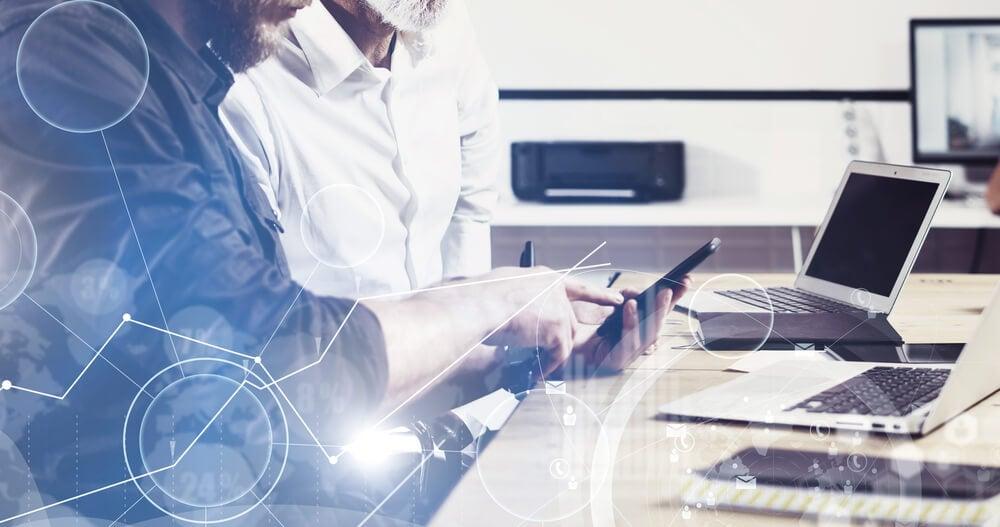 sobreposição de imagens de dispositivos eletronicos sob mesa de escritório e gráficos