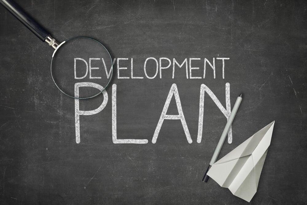 título plano de desenvolvimento junto de lupa e avião de papel