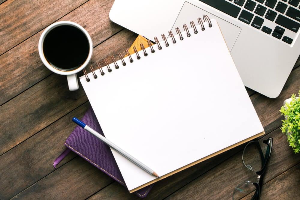 xícara de café junto de cadernos de anotação para processo importante para a criatividade