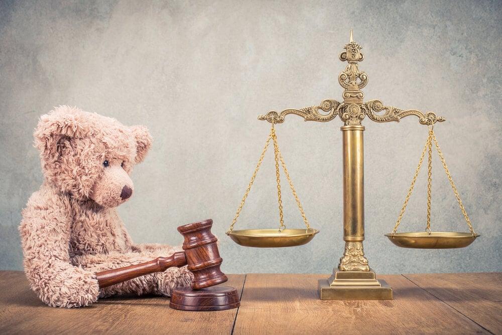 balança de justiça e ursinho demonstrando leis no cenário infantil