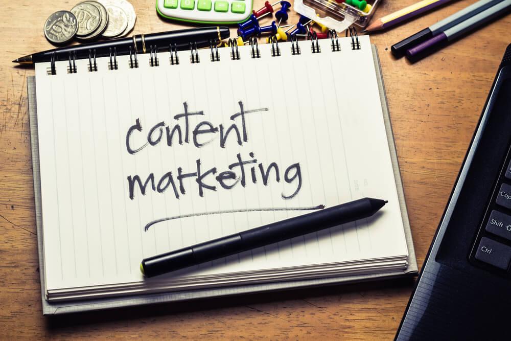 bloco de notas com materiais de escritorio em volta com a frase content marketing escrita