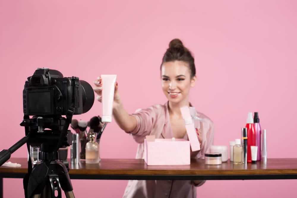 blogueira criando conteudo de video mostrando produtos de beleza em frente a camera profissional