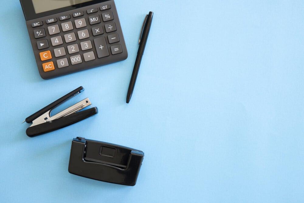 calculadora e materiais de escritorio em fundo azul