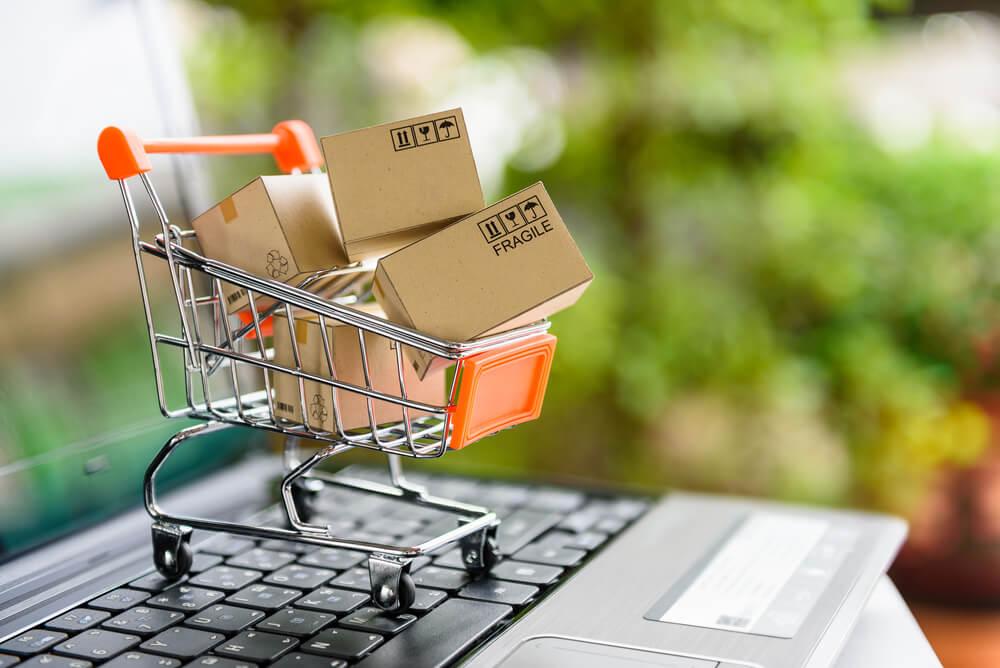 carrinho de compras e caixas em cima de teclado de laptop