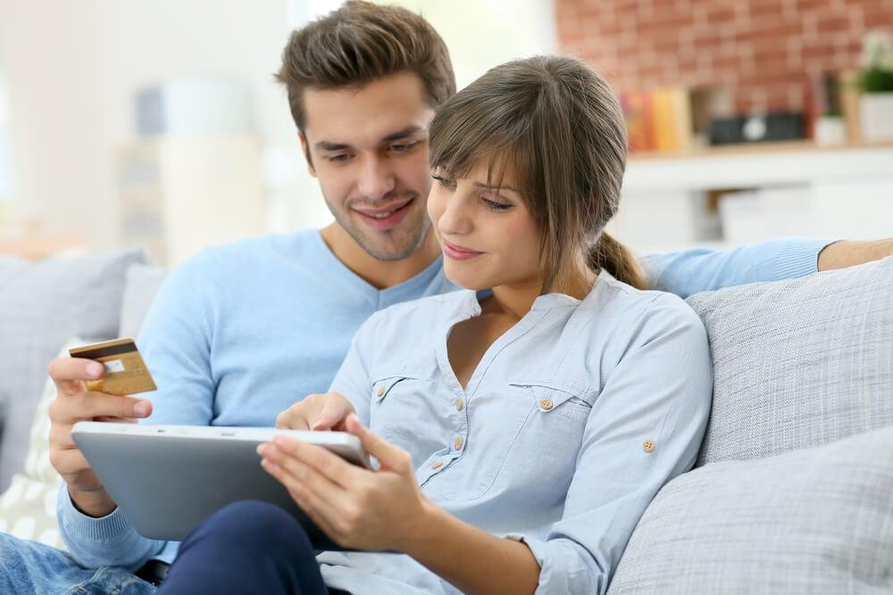 casal acessando laptop junto de cartão de crédito em mãos