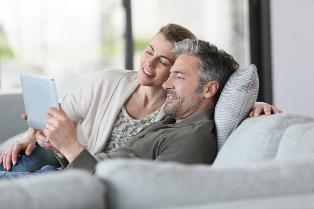 casal sentado em sofá em contato com a era digital por meio de uma tablet