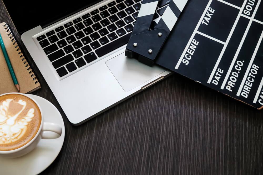 claquete junto de xícara de café e laptop